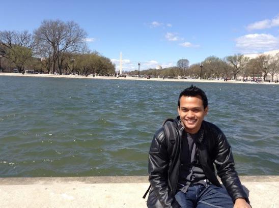 Duduk di sisi kolam buatan depan U.S. Capitol dengan background Obelisk
